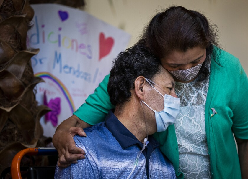 Armando Mendoza, 53, of Anaheim, who spent 45 days at St. Joseph Hospital battling COVID-19, hugs his wife Lilia after he was released Tuesday.