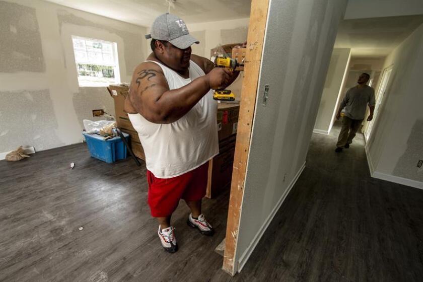 El hondureño Randy Álvarez (i) realiza trabajos de remodelación en su vivienda ayer domingo, 19 de agosto de 2018, en el oeste de Houston, Texas (EE.UU.). EFE