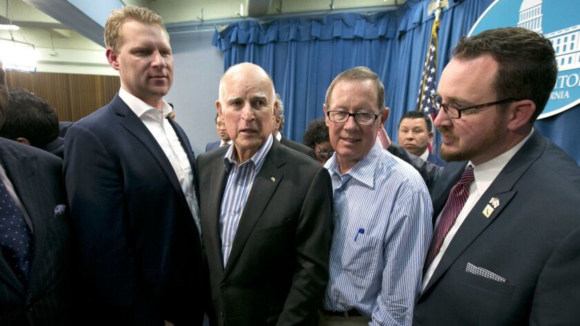 Gov. Jerry Brown, second from left, flanked by Republicans, Assembly Leader Chad Mayes, of Yucca Valley, left, Tom Berryhill, of Twain Harte, and Devon Mathis, of Visalia, right, on July 17, 2017.