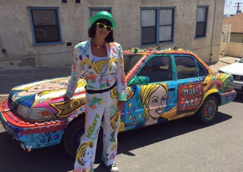"""Gretchen Baer stands in front of her car in front of her """"Hillcar"""" that she drives from campaign stop to campaign stop."""