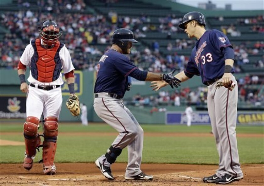 Minnesota Twins designated hitter Ryan Doumit is greeted at the plate by Justin Morneau (33) after his two-run home run as Boston Red Sox catcher Jarrod Saltalamacchia walks back to position during the first inning of a baseball game at Fenway Park in Boston, Wednesday, May 8, 2013. (AP Photo/Elise Amendola)