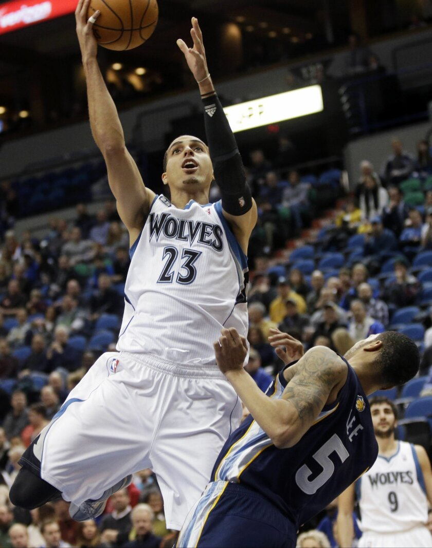 Minnesota Timberwolves' Corey Brewer lays up a basket as Memphis Grizzlies' Courtney Lee falls backward in the first quarter of an NBA basketball game on Friday, Jan. 31, 2014, in Minneapolis. (AP Photo/Jim Mone)