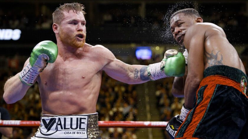 Canelo Alvarez, left, hits Daniel Jacobs during a middleweight title boxing match on May 4 in Las Vegas.