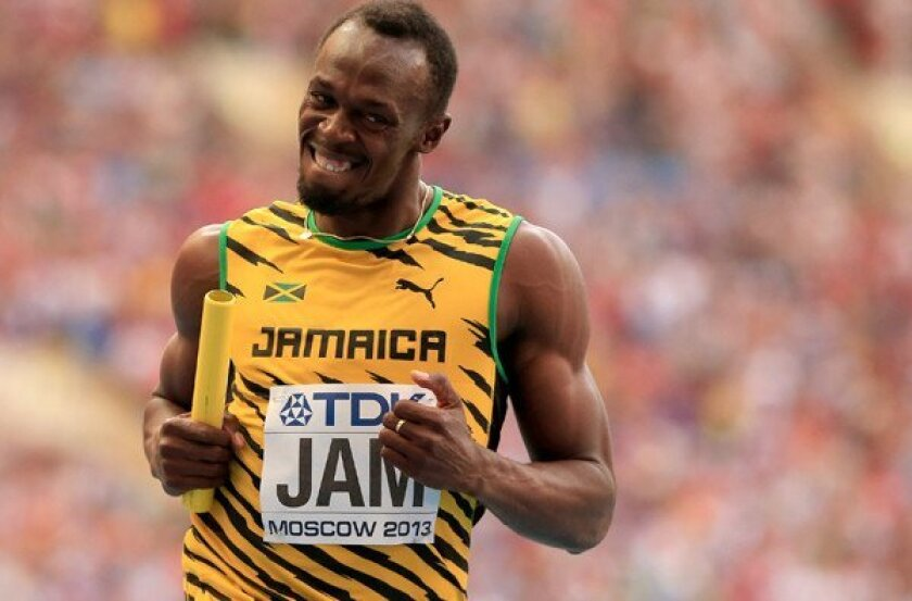 Usain Bolt flashes a grin as he crosses the finish line to give Jamaica the win in the 400-meter relay Sunday at the world track championships.