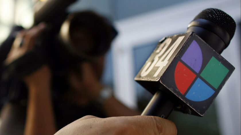 FILE- In this June 14, 2006, file photo a journalist holds a microphone bearing the Univision logo i