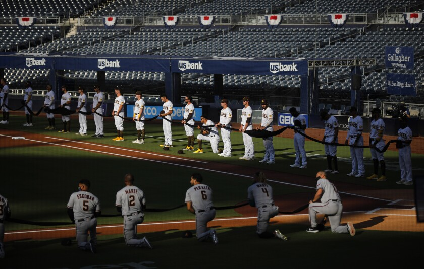Players line the field honoring the Black Lives Matter movement before the Padres played Arizona.