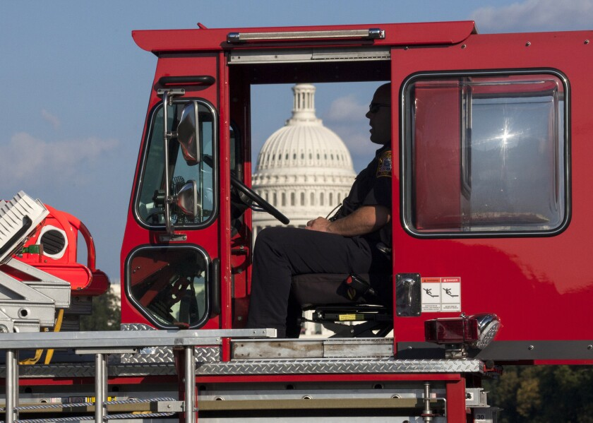 A firefighter sits in a fire truck near the scene on the National Mall in Washington, where, according to a fire official, a man set himself on fire Friday, Oct. 4, 2013. The official said the man was flown by helicopter to a hospital.
