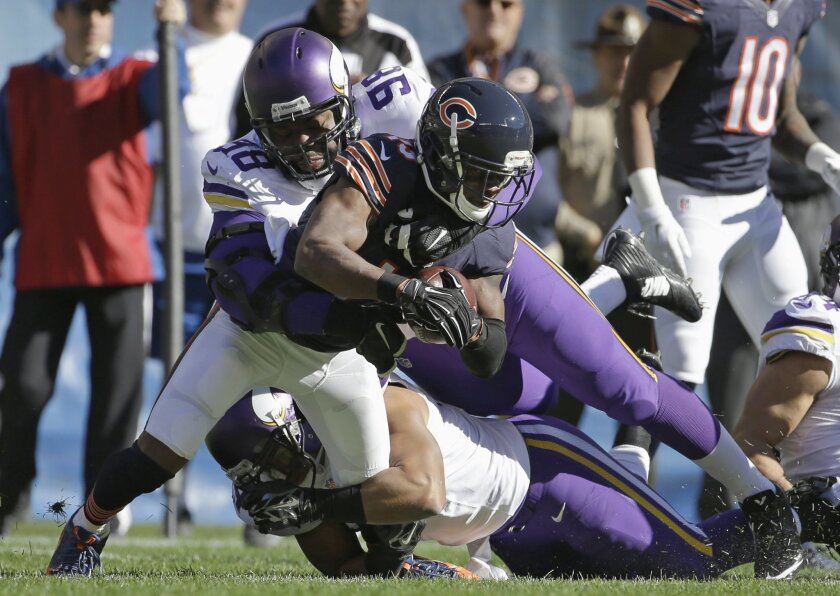 Minnesota Vikings defensive tackle Linval Joseph (98) and linebacker Eric Kendricks tackle Chicago Bears receiver Eddie Royal (19) during the first half of an NFL football game, Sunday, Nov. 1, 2015, in Chicago. (AP Photo/Nam Y. Huh)