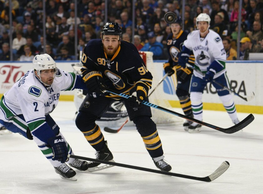 Vancouver Canucks defenseman Dan Hamhuis (2) arrives too late as Buffalo Sabres center Ryan O'Reilly (90) clears the puck during the second period of an NHL hockey game, Saturday Nov. 7, 2015, in Buffalo, N.Y. (AP Photo/Gary Wiepert)