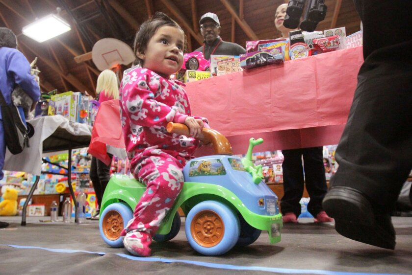 Silvia Carrillo, age 1, rides her new toy at the Rock Church's annual Toys for Joy event at Lincoln High School. Thousands of kids received toys at the event
