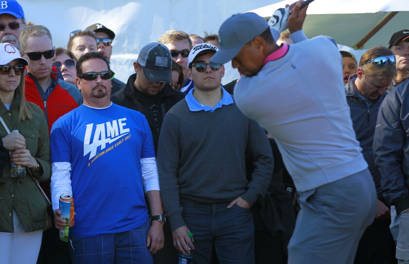 A fan wearing his thoughts on the Chargers' move looks on as Tiger Woods warms up on the 17th hole of the North Course at Torrey Pines Golf Course during the second round of the Farmers Insurance Open.
