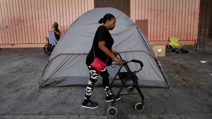 LOS ANGELES, CA SEPTEMBEFR 12, 2018: Royce Cutrer, 54, uses a walker as she walks past a tent in t