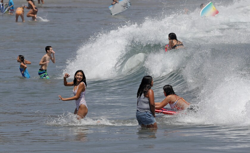 Children jump into the waves at Corona del Mar State Beach in Newport Beach on Tuesday.