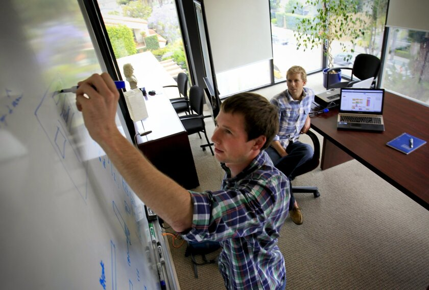 Russell McLoughlin, left, and Ethan Senturia, right, co-founders of Dealstruck, a crowd funding marketplace that connects established, growing, small and medium size businesses with individual and institutional investors who want to lend money to those businesses, work on a workflow diagram.