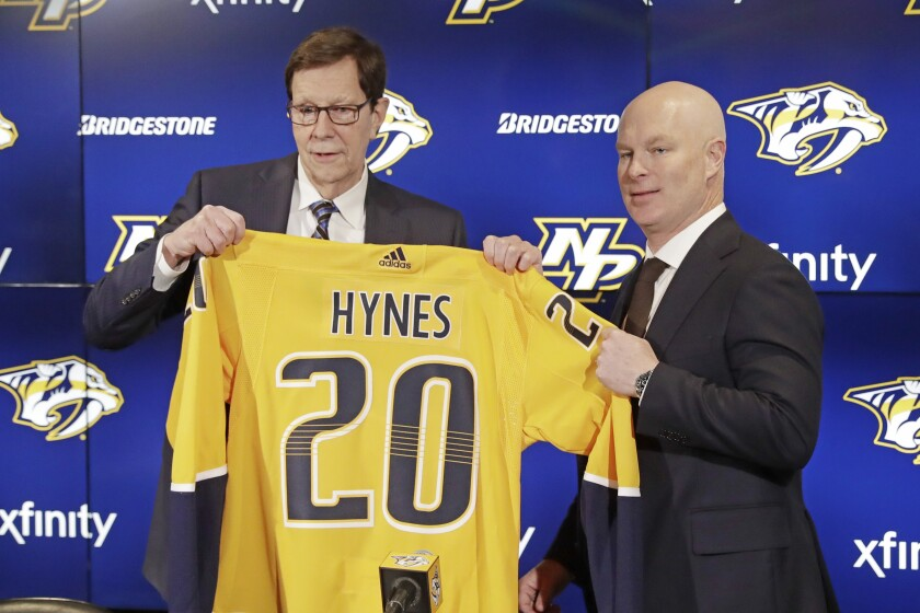 New Nashville Predators NHL hockey team head coach John Hynes, right, poses for photos with Predators general manager David Poile at a news conference Tuesday, Jan. 7, 2020, in Nashville, Tenn. The Predators hired Hynes, the former New Jersey Devils coach, as the third coach in franchise history after firing Peter Laviolette. (AP Photo/Mark Humphrey)