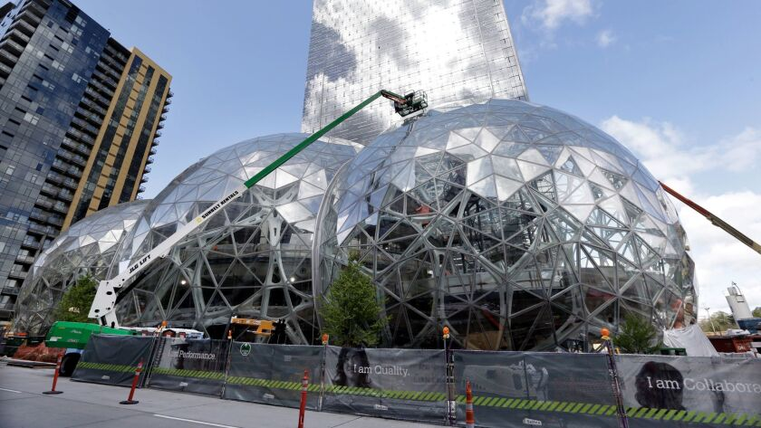 Three large glass domes mark where Amazon is expanding its Seattle headquarters; now it wants to build a second HQ in a city to be named later. How much will be bid?