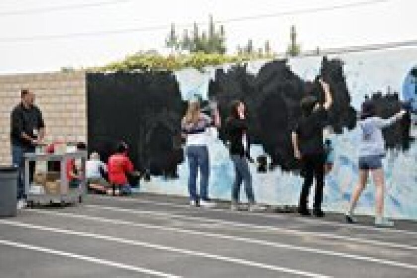 Students paint alongside Roberto Salas in the developing mural.