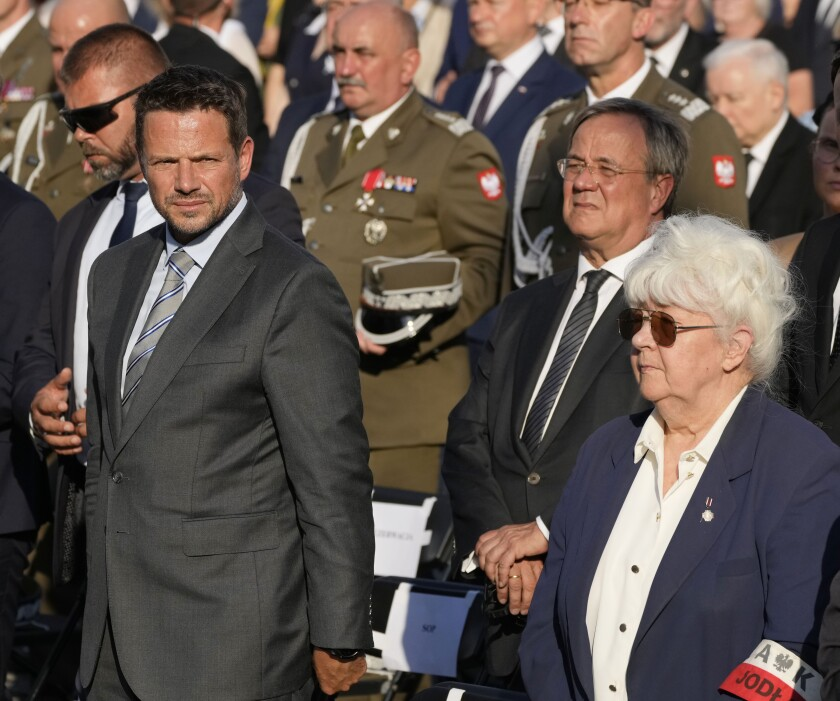"""Germany's center-right candidate to replace Angela Merkel as chancellor in the upcoming elections, Armin Laschet, second right, and the Warsaw Mayor Rafal Trzaskowski, left, as they attend observances marking the 77th anniversary of the ill-fated 1944 Warsaw Rising against the occupying Nazi Germans, in Warsaw, Poland, on Saturday, July 31, 2021. Laschet said in an interview he feels """"deep shame and humility"""" over Nazi Germany's """"crimes"""" against the Poles during World War II.(AP Photo/Czarek Sokolowski)"""