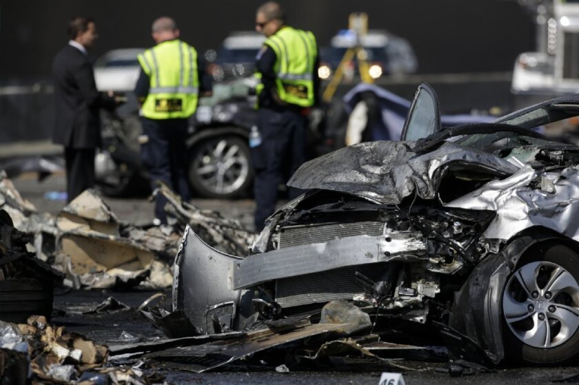 California Highway Patrol investigators probe the scene of a fiery crash on the 5 Freeway that left three people dead in Commerce earlier this year. Police believe the wreck was due to illegal street racing.