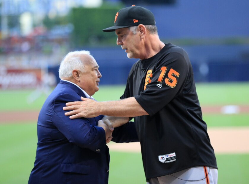 Padres Executive Chairman Ron Fowler congratulates manager Bruce Bochy of the San Francisco Giants on his upcoming retirement during a pregame ceremony July 26 at Petco Park.