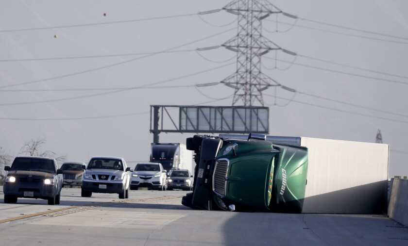 A truck lies on its side after being overturned by high winds on the southbound 15 Freeway near Duncan Canyon Road on Tuesday morning in Fontana.