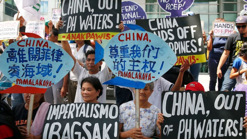 Protesters display placards during a rally at the Chinese Consulate to protest China's artificial is