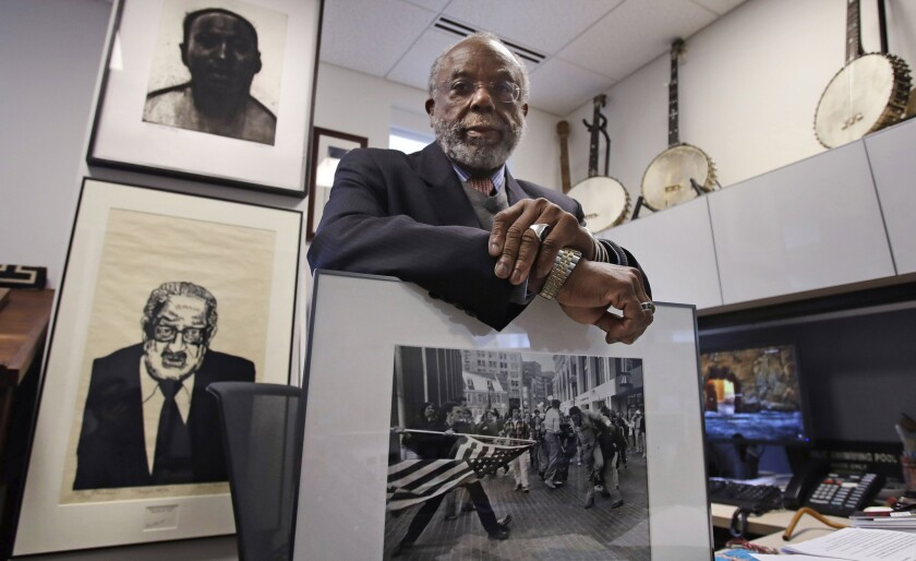 Theodore Landsmark, lawyer, architect and director of the Dukakis Center for Urban and Regional Policy at Northeastern University poses for a photo in his office in Boston, Tuesday, March 27, 2018. Pictured in Landsmark's office are a sketch of King, top left, a portrait of Supreme Court Justice Thurgood Marshall, bottom left, and a Pulitzer Prize-winning photograph by Stanley Forman, which shows Landsmark being assaulted in 1976 by a demonstrator carrying a flagpole bearing the American flag.