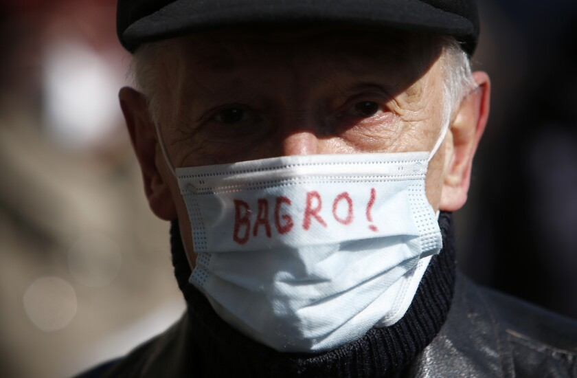A man wearing a face mask reads: ''Scum!'' to protect against coronavirus attends during protest in front of the government building in Belgrade, Serbia, Monday, Feb. 15, 2021. Hundreds gathered outside the government headquarters to honor dozens of medical staff who died since the start of the outbreak. (AP Photo/Darko Vojinovic)