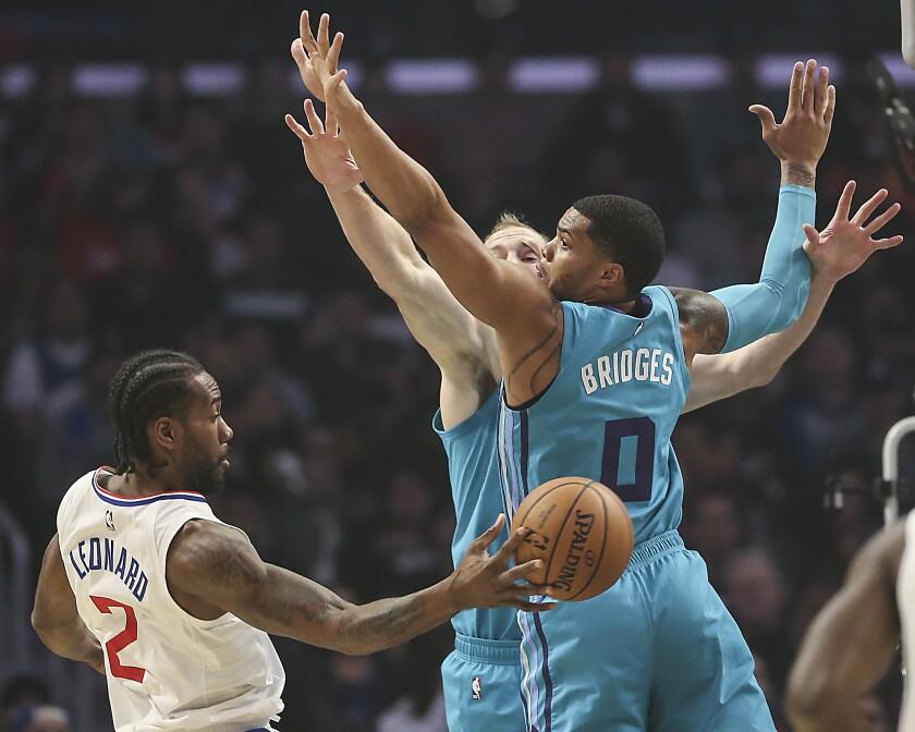 Clippers star Kawhi Leonard passes behind Charlotte Hornets defenders Cody Zeller and Miles Bridges.
