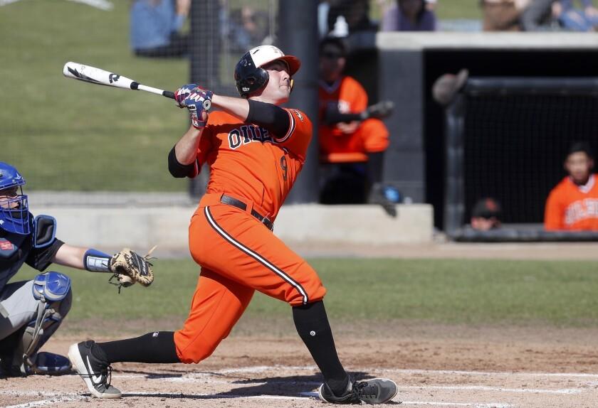 Huntington Beach High's Josh Hahn hits the ball deep in right field for a triple against Fountain Va