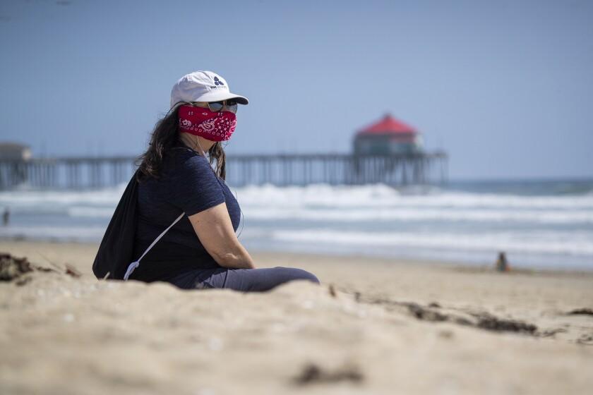 Huntington Beach resident Kelly Beita wears a bandanna as she takes a beachside break.
