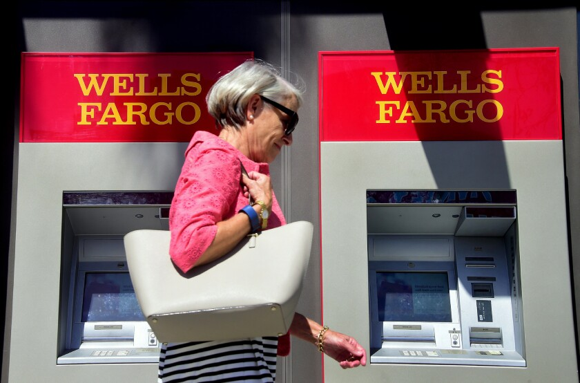 A woman walks past a Wells Fargo ATM in Pasadena in September.
