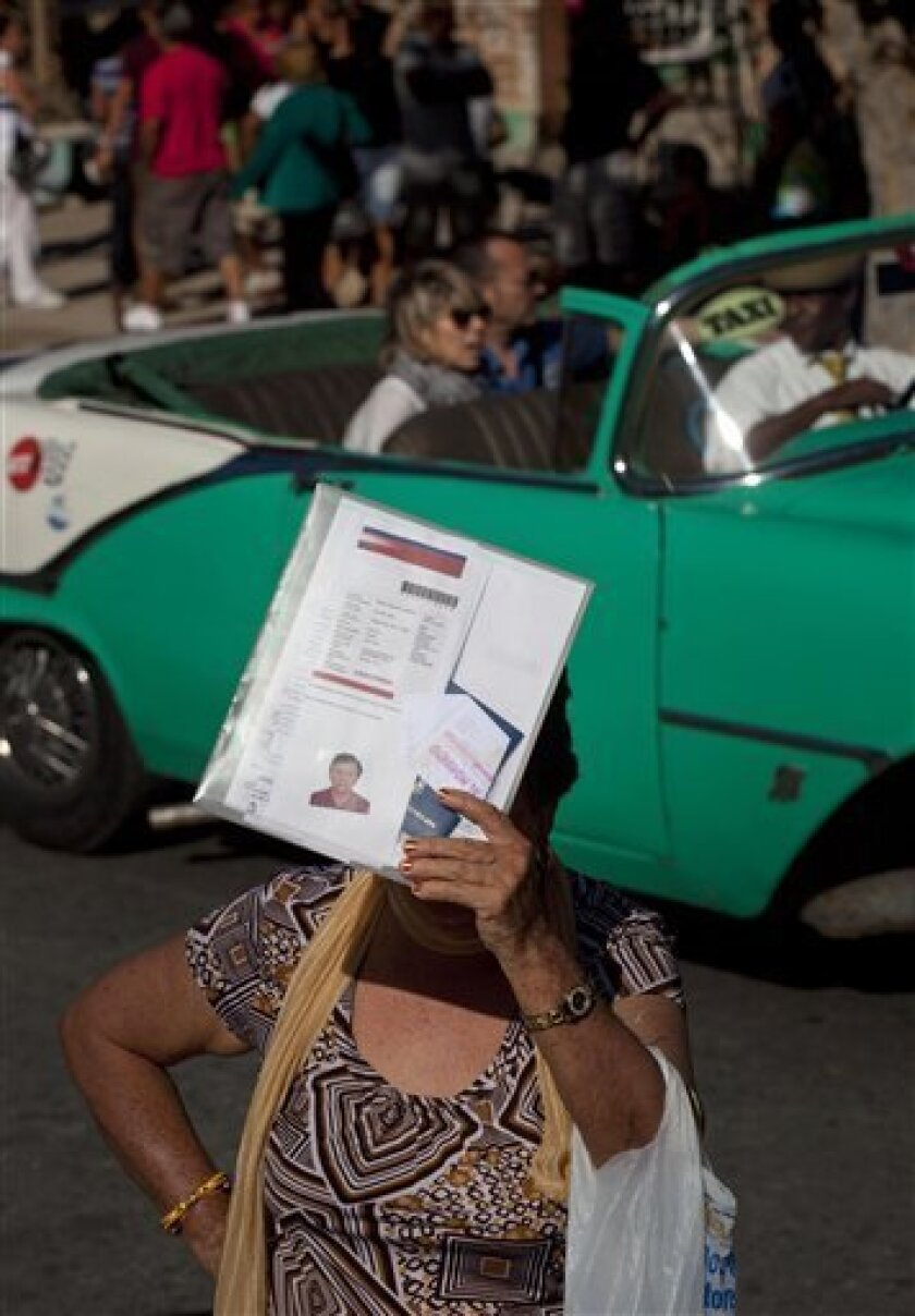 In this Jan 14, 2013 file photo, a woman shades herself with her documents as she waits outside the U.S. Interests Section to apply for U.S. visas in Havana, Cuba. The number of Cubans receiving U.S. nonimmigrant visas jumped by 79 percent in the first half of the year, Communist Party newspaper Granma reported Friday, Aug. 2, 2013. (AP Photo/Ramon Espinosa, File)