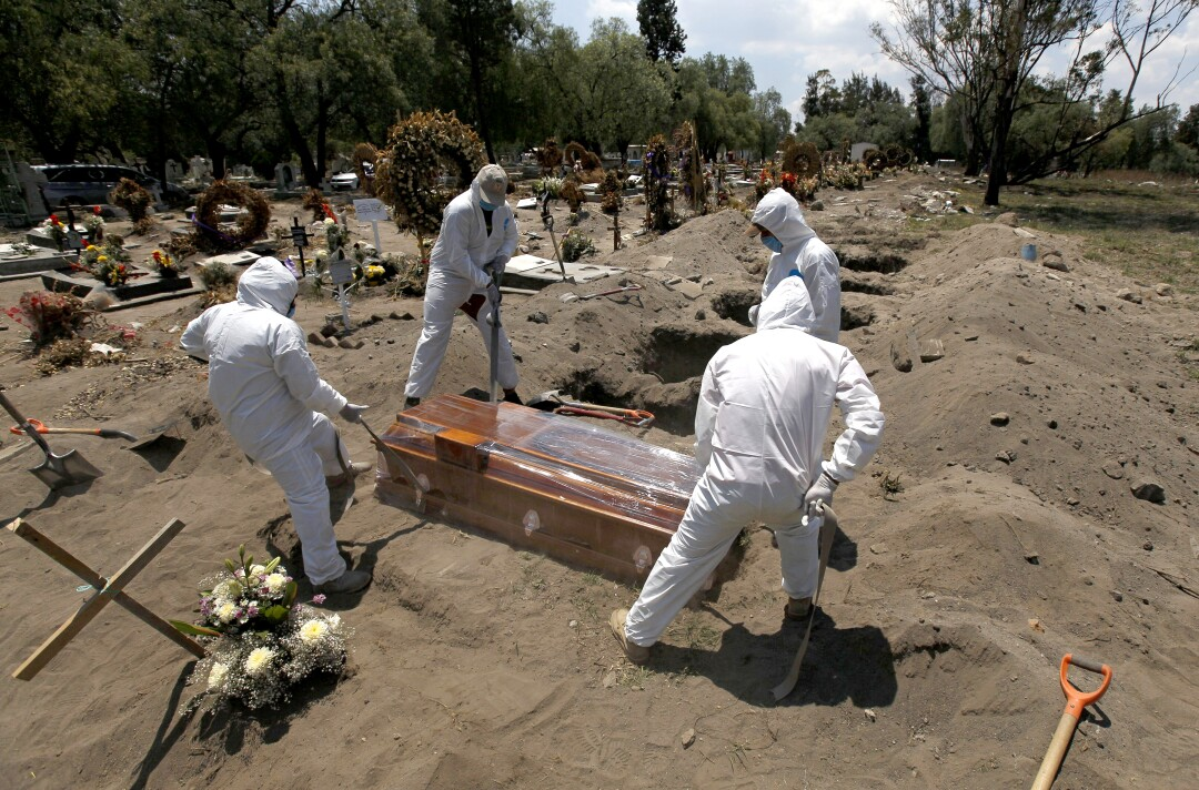 Cemetery workers in a protective gear lower the coffin of a COVID-19 victim into the ground in Mexico City.