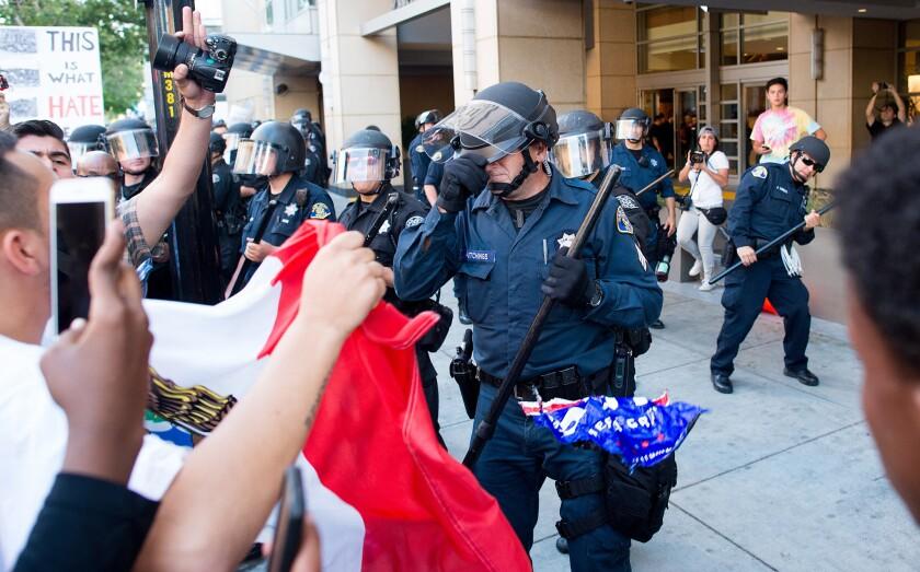 Un policía se cubre el rostro mientras los manifestantes arrojan objetos a los agentes a las afueras de un acto de campaña del precandidato presidencial republicano, Donald Trump, el jueves 2 de junio de 2016, en San Jose, California. Un grupo de manifestantes atacaron a personas a favor de Trump que salían del acto del precandidato en San Jose el jueves por la noche. Unas 12 personas fueron golpeadas, al menos una persona fue golpeada por un huevo, y las gorras que les quitaron a los seguidores de Trump fueron quemadas. (AP Foto/Noah Berger)