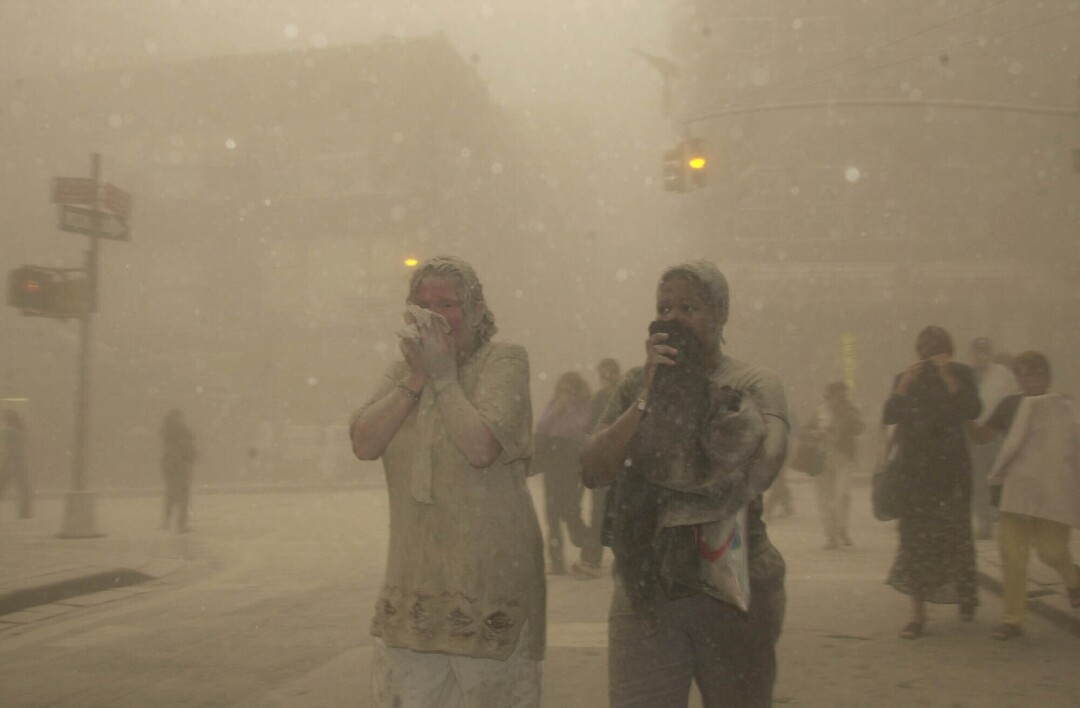 People shrouded by smoky air cover their mouths as they walk in the street