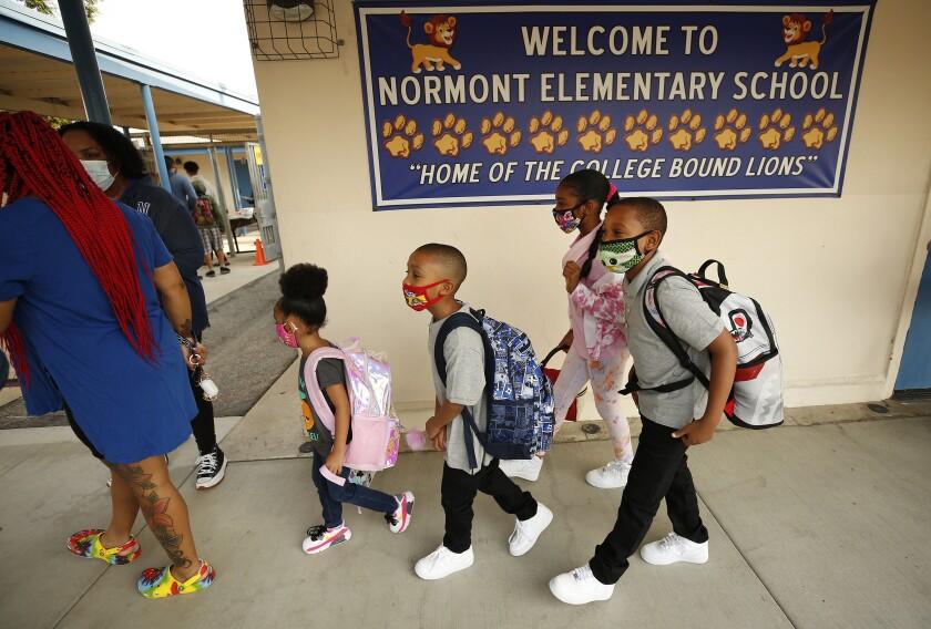 Students walk into their elementary school.