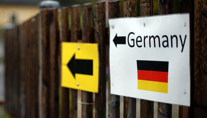 FILE - In this Thursday, Oct. 15, 2015 file photo signs are attached on a fence at the border between Austria and Germany in Wegscheid near Passau, Germany. Germany's population has contracted slightly for the first time in nearly a decade because immigration shrank as a result of the coronavirus pandemic, official data showed Tuesday. (AP Photo/Matthias Schrader, file)
