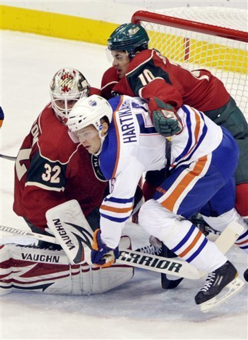Minnesota wild goalie Niklas Backstrom, left, of Finland, gets some added defensive help from Devin Setoguchi, top right, as they attempt to keep Edmonton Oilers Teemu Hartikainen in check in the first period of an NHL preseason hockey game on Friday, Sept. 30, 2011, in St Paul, Minn. (AP Photo/Jim Mone)
