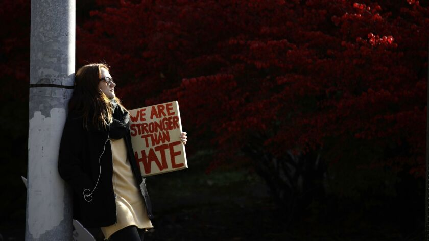 A demonstrator waits for the start of a protest in the aftermath of the mass shooting at the Tree of