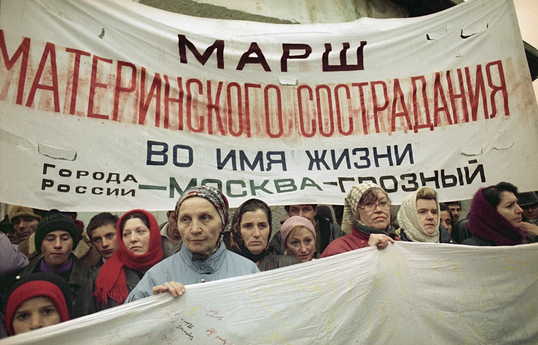 Mothers of Russian soldiers carry a protest banner in 1995. The banner says: