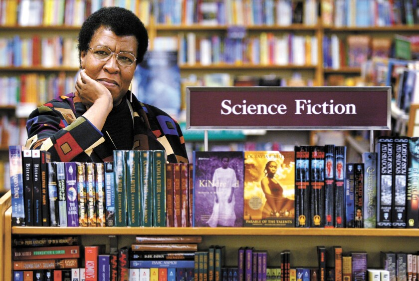 Octavia Butler by a bookcase of her novels