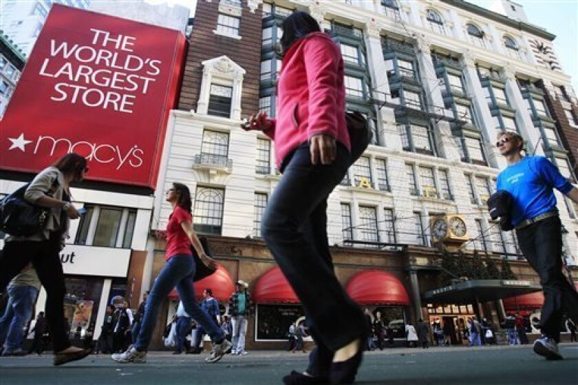 FILE - In this Nov. 8, 2011, file photo, pedestrians pass the Macy's department store, in New York. Macy's Inc. is reporting quarterly earnings on Wednesday, Aug. 14, 2013. (AP Photo/Frank Franklin II, File)