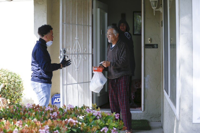 Rev. Shane Harris (left) delivered grocery items to Habib Alim and his wife, Fatima Wahidi, in Tierrasanta in March