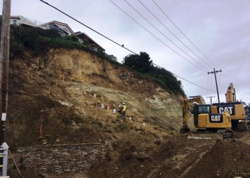 Workers with heavy equipment reconstruct a slope along Jimmy Durante Boulevard in Del Mar.