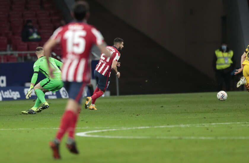 Atletico Madrid's Yannick Carrasco takes the ball away from Barcelona's goalkeeper Marc-Andre ter Stegen to score his side's opening goal during the Spanish La Liga soccer match between Atletico Madrid and FC Barcelona at the Wanda Metropolitano stadium in Madrid, Spain, Saturday, Nov. 21, 2020. (AP Photo/Bernat Armangue)
