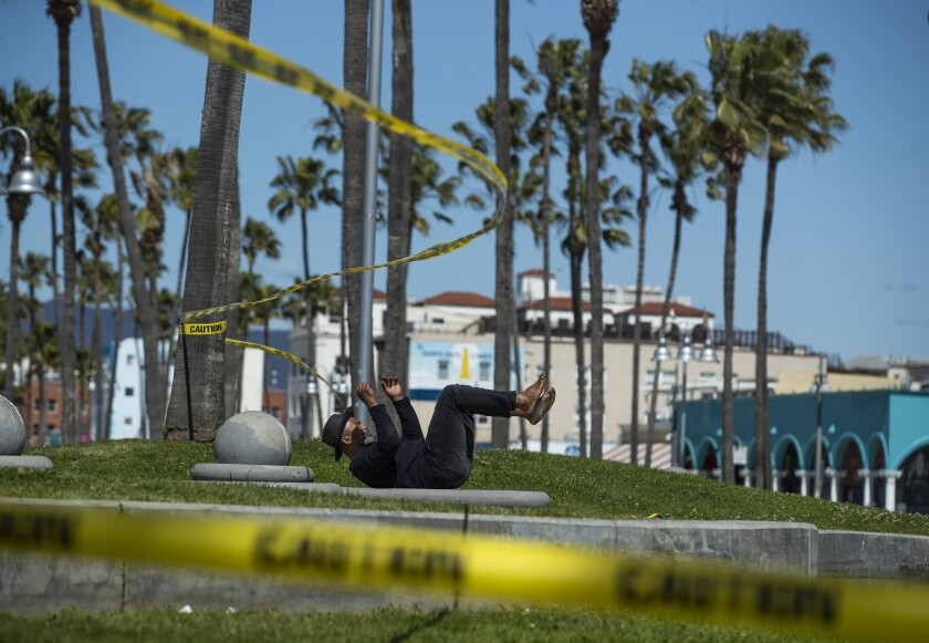 Raymond Bartlett exercises near caution tape at the basketball courts at Venice Beach.