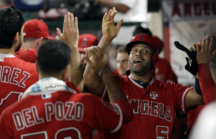 Angels slugger Albert Pujols celebrates in the dugout after scoring a run during the seventh inning against the Rangers on Tuesday.