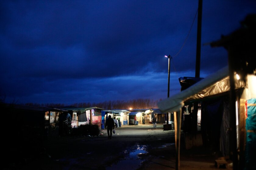 In this Feb. 4, 2016 photo, a person walks through the migrant camp in Calais, north of France. Mysterious armed groups are on the prowl, targeting migrants in night attacks in Calais and other migrant haunts in northern France, sowing fear among the displaced travelers living in squalid slums in h