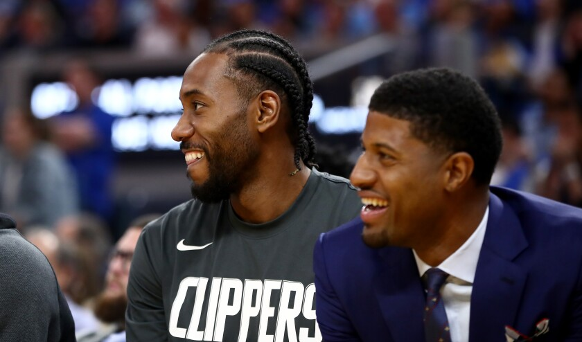 Clippers forwards Kawhi Leonard, left, and Paul George share a laugh during the blowout victory over the Warriors.